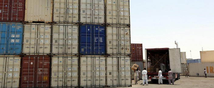 Iranian workers transfer goods from a cargo container to trucks at the Kalantari port in the city of Chabahar. (ATTA KENARE/AFP/Getty Images)