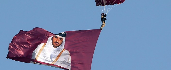 A paraglider, with the image of Emir of Qatar Sheikh Tamim Bin Hamad al-Thani, glides over the capital during the Gulf emirate's National Day celebrations in Doha, on December 18, 2013. (KARIM JAAFAR/AFP/Getty Images)