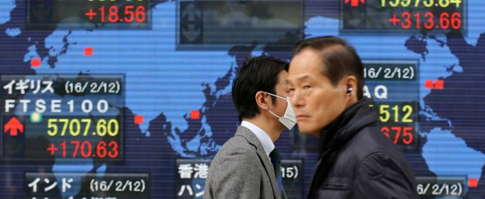 People walk by an electronic stock board of a securities firm, in Tokyo on February 15. The realization is dawning that growth may continue to underperform, while in Japan the yield on 10-year bonds briefly turned negative. (AP Photo/Koji Sasahara)