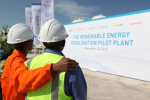 Laborers look toward a sign at a desalination test facility near Abu Dhabi, United Arab Emirates,  Nov. 23, 2015. (AP Photo/Jon Gambrell)