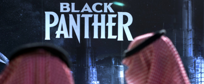"Saudis stand in front of banner for ""Black Panther"""