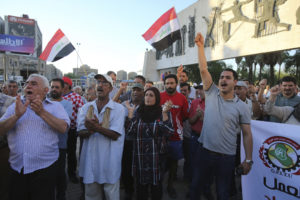Protesters chant slogans demanding services as they wave national flags during a demonstration in Tahrir Square in Baghdad, Iraq, Aug. 10. (AP Photo/Karim Kadim)